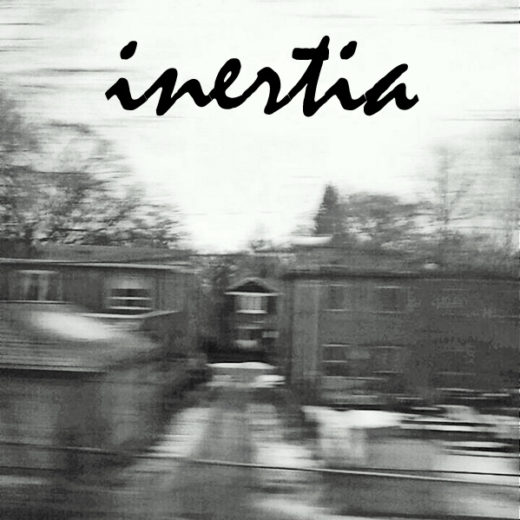 a motion-blurred picture of houses with the word Inertia overtop