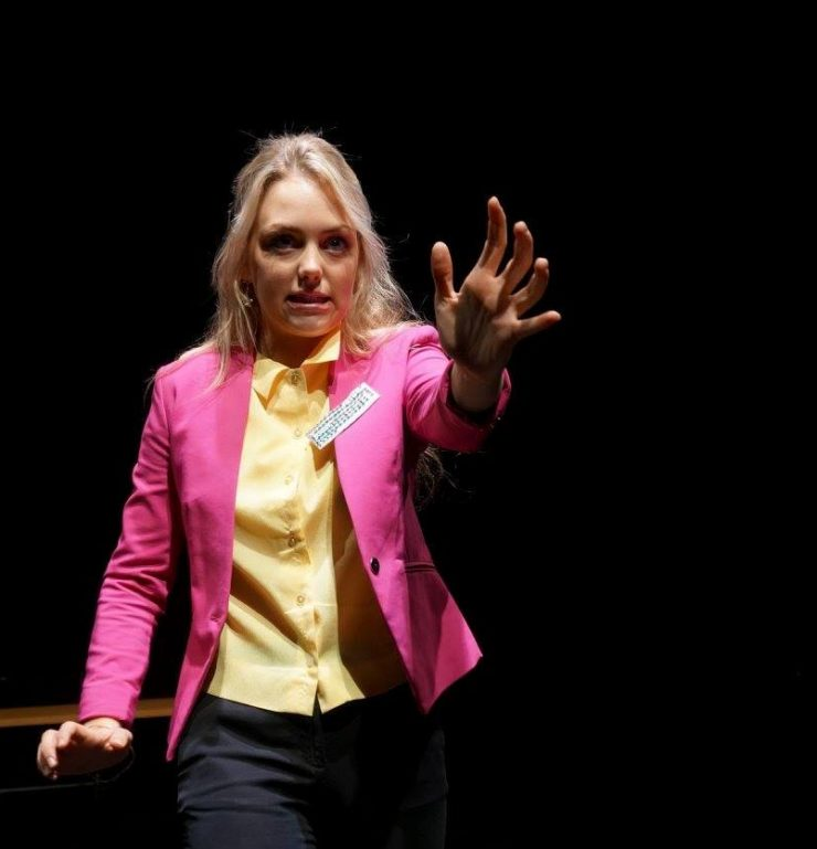 a woman in a pink blazer with her hand outstretched