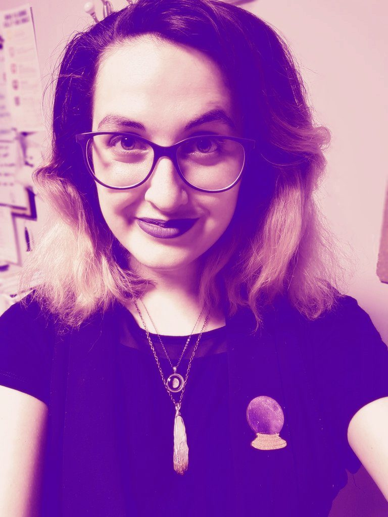 A selfie of Jillian. She has dark to light ombre hair. She is wearing glasses, dark lipstick, 2 necklaces, a crystal ball pin and a black tshirt. The colour has been edited to be only purple.